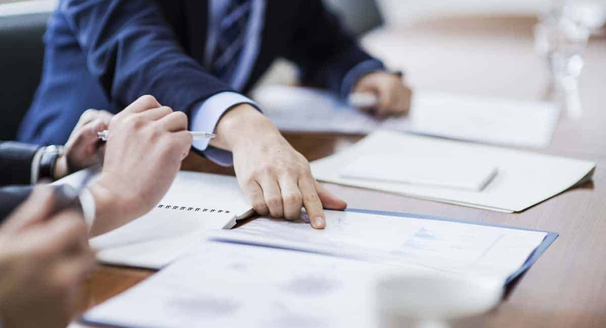 business man pointing at documents on a conference room table.