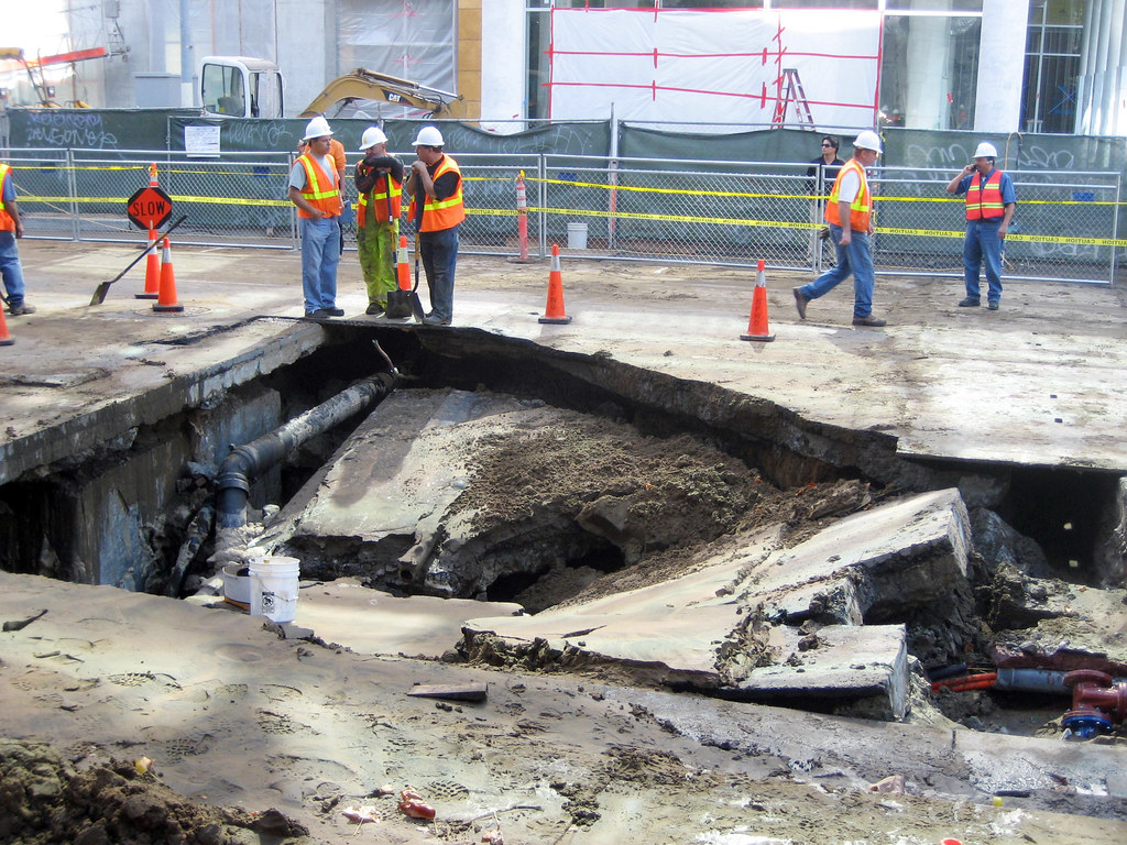 workers surround sinkhole damage as they assess how to resolve the issue.