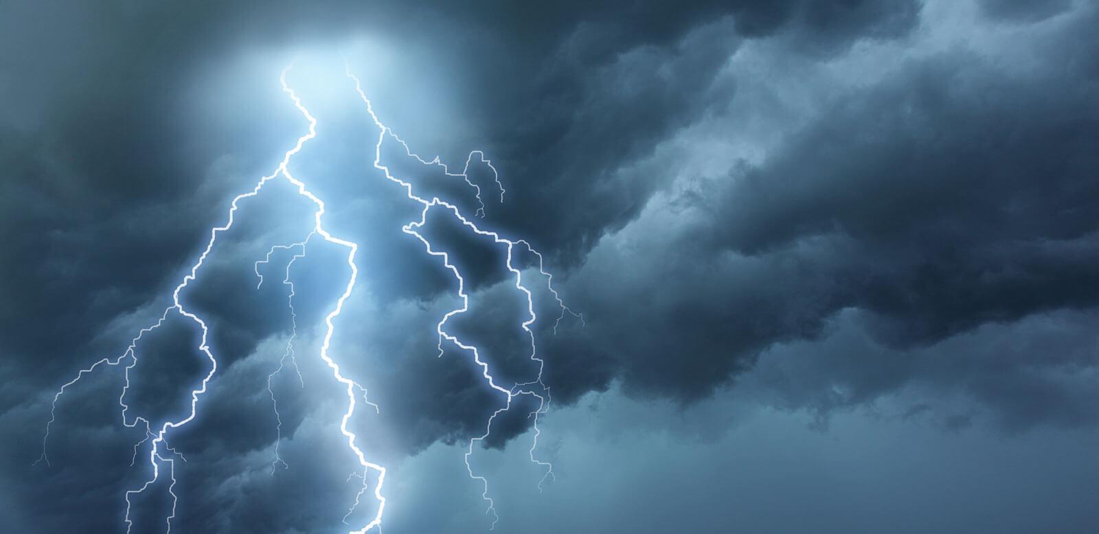 lightning cracks across blue sky at night