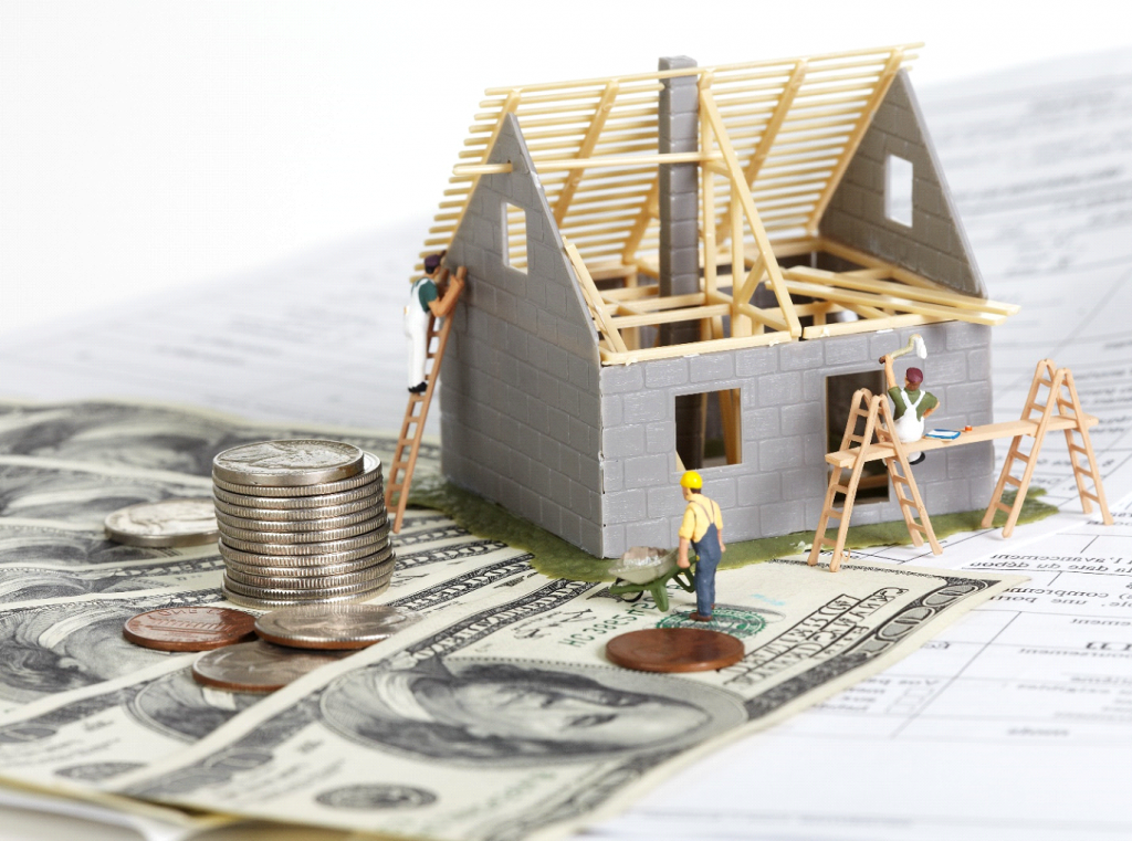 graphic of workers building a home on top of dollar bills and change.